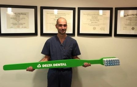 in-network dentist holding life size Delta Dental toothbrush