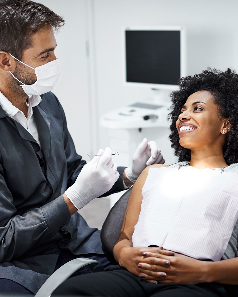 Smiling woman reclines back in dentist chair as the dentist prepares to take a look at her teeth with his instruments