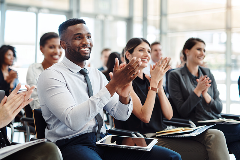 Group of sitting employees smile and clap as they listen to a presentation in front of them